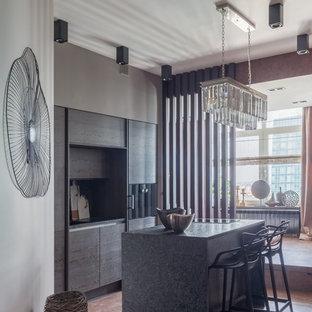 На фото: параллельная кухня-гостиная среднего размера в современном стиле с врезной раковиной, плоскими фасадами, темными деревянными фасадами, гранитной столешницей, черным фартуком, фартуком из каменной плиты, черной техникой, пробковым полом, островом, коричневым полом и черной столешницей с