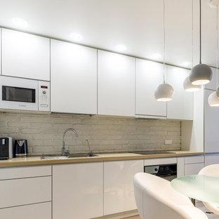 サンクトペテルブルクの中サイズのコンテンポラリースタイルのおしゃれなキッチン (シングルシンク、フラットパネル扉のキャビネット、白いキャビネット、木材カウンター、白いキッチンパネル、レンガのキッチンパネル、カラー調理設備、ラミネートの床、ベージュの床) の写真