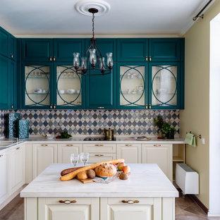 На фото: угловая кухня в классическом стиле с накладной раковиной, стеклянными фасадами, бирюзовыми фасадами, разноцветным фартуком, белой техникой, островом, коричневым полом и белой столешницей