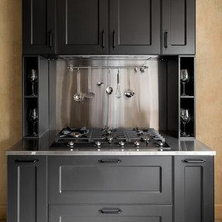 Rustik inredning av ett mellanstort grå linjärt grått kök och matrum, med en dubbel diskho, luckor med infälld panel, svarta skåp, bänkskiva i rostfritt stål, grått stänkskydd, stänkskydd i metallkakel, svarta vitvaror, klinkergolv i porslin och vitt golv