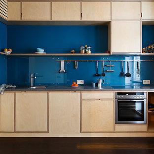 Свежая идея для дизайна: угловая кухня в скандинавском стиле с плоскими фасадами, столешницей из бетона, синим фартуком, фартуком из стекла, техникой из нержавеющей стали, темным паркетным полом, коричневым полом, серой столешницей и светлыми деревянными фасадами без острова - отличное фото интерьера
