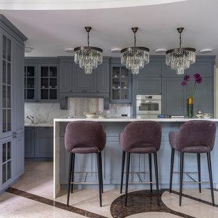 На фото: параллельная кухня в классическом стиле с фасадами с выступающей филенкой, синими фасадами, белым фартуком, фартуком из каменной плиты, островом, бежевым полом и белой столешницей с