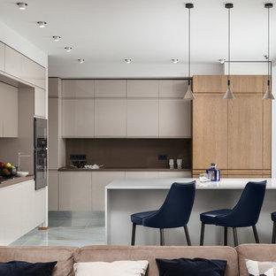 Пример оригинального дизайна интерьера: кухня-гостиная в современном стиле с плоскими фасадами, бежевыми фасадами, коричневым фартуком, полуостровом, белым полом и коричневой столешницей