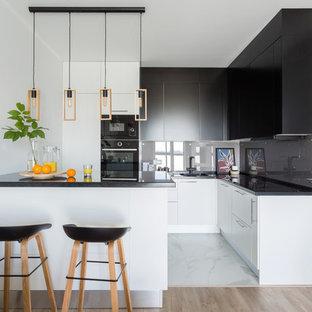 Свежая идея для дизайна: угловая кухня в скандинавском стиле с плоскими фасадами, серым фартуком, фартуком из стекла, черной техникой, белым полом, черной столешницей, одинарной раковиной, черными фасадами и полуостровом - отличное фото интерьера