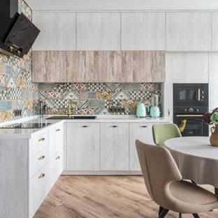 Пример оригинального дизайна: угловая кухня в современном стиле с обеденным столом, накладной раковиной, плоскими фасадами, серыми фасадами, разноцветным фартуком, черной техникой, коричневым полом и белой столешницей без острова