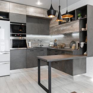Idéer för ett avskilt, litet industriellt grå l-kök, med en nedsänkt diskho, släta luckor, grå skåp, bänkskiva i koppar, stänkskydd i trä, laminatgolv, grått golv, grått stänkskydd, vita vitvaror och en halv köksö