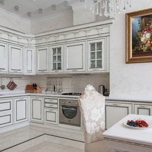 Создайте стильный интерьер: угловая кухня в стиле современная классика с обеденным столом, двойной раковиной, белыми фасадами, фартуком из плитки мозаики, техникой из нержавеющей стали, мраморным полом, бежевым полом и бежевым фартуком - последний тренд