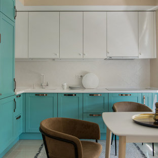 Design ideas for a mid-sized eclectic l-shaped eat-in kitchen in Moscow with an integrated sink, raised-panel cabinets, turquoise cabinets, solid surface benchtops, white splashback, ceramic splashback, stainless steel appliances, porcelain floors, no island, beige floor and white benchtop.