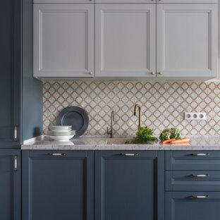 Bild på ett mellanstort vintage beige linjärt beige kök och matrum, med en undermonterad diskho, luckor med upphöjd panel, grå skåp, bänkskiva i kvarts, beige stänkskydd, stänkskydd i marmor, rostfria vitvaror, klinkergolv i keramik och brunt golv