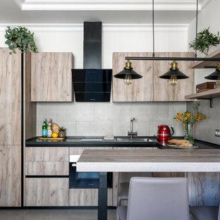Идея дизайна: п-образная кухня в современном стиле с накладной раковиной, плоскими фасадами, светлыми деревянными фасадами, серым фартуком, техникой из нержавеющей стали, полуостровом, серым полом, черной столешницей и многоуровневым потолком