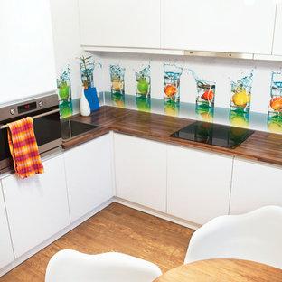 モスクワの小さいコンテンポラリースタイルのおしゃれなキッチン (ドロップインシンク、フラットパネル扉のキャビネット、白いキャビネット、ガラス板のキッチンパネル、シルバーの調理設備、アイランドなし、マルチカラーのキッチンパネル、木材カウンター) の写真