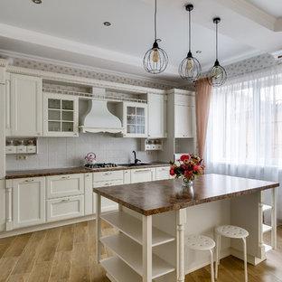 Выдающиеся фото от архитекторов и дизайнеров интерьера: линейная кухня в классическом стиле с накладной раковиной, фасадами с утопленной филенкой, белыми фасадами, белым фартуком, островом, коричневым полом и коричневой столешницей