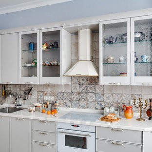 На фото: большая угловая кухня в стиле неоклассика (современная классика) с серыми фасадами, фартуком из керамической плитки, белой техникой, белой столешницей, разноцветным фартуком, обеденным столом, врезной раковиной, стеклянными фасадами, столешницей из акрилового камня, полом из керамической плитки и оранжевым полом с