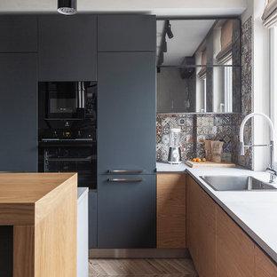Стильный дизайн: угловая кухня в современном стиле с накладной раковиной, плоскими фасадами, фасадами цвета дерева среднего тона, разноцветным фартуком, черной техникой, островом, коричневым полом и белой столешницей - последний тренд