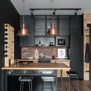 Inredning av ett industriellt litet gul linjärt gult kök med öppen planlösning, med en nedsänkt diskho, luckor med glaspanel, svarta skåp, träbänkskiva, svart stänkskydd, stänkskydd i trä, svarta vitvaror, klinkergolv i porslin, en köksö och brunt golv