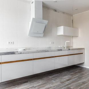 На фото: прямая кухня в современном стиле с врезной раковиной, плоскими фасадами, белыми фасадами, мраморной столешницей, белым фартуком, коричневым полом и серой столешницей без острова с