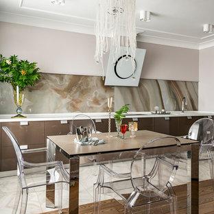 На фото: большая угловая кухня в современном стиле с обеденным столом, плоскими фасадами, столешницей из акрилового камня, фартуком из керамогранитной плитки, белой столешницей, коричневыми фасадами, коричневым фартуком, черной техникой и бежевым полом без острова