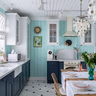На фото: кухни в морском стиле с обеденным столом, раковиной в стиле кантри, синими фасадами, разноцветным полом, белой столешницей, фасадами с утопленной филенкой и белой техникой