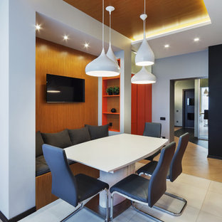 Неиссякаемый источник вдохновения для домашнего уюта: параллельная кухня среднего размера в современном стиле с обеденным столом, врезной раковиной, плоскими фасадами, оранжевыми фасадами, столешницей из акрилового камня, черным фартуком, фартуком из керамогранитной плитки, черной техникой, полом из керамогранита и белым полом