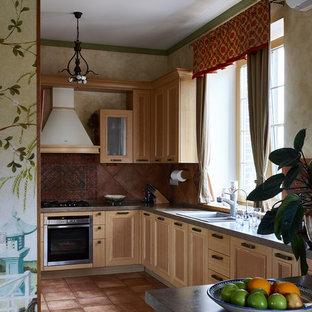 На фото: п-образная кухня в стиле кантри с светлыми деревянными фасадами, коричневым фартуком, техникой из нержавеющей стали и полуостровом с