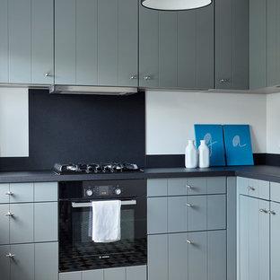 Создайте стильный интерьер: угловая кухня среднего размера в стиле современная классика с плоскими фасадами, серыми фасадами, черным фартуком, черной техникой, полом из керамической плитки и разноцветным полом - последний тренд