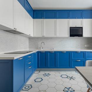 На фото: угловая кухня среднего размера в современном стиле с накладной раковиной, фасадами с утопленной филенкой, синими фасадами, белым фартуком и белой столешницей без острова