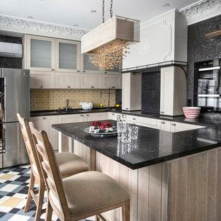 Новые идеи обустройства дома: большая п-образная кухня-гостиная в стиле современная классика с врезной раковиной, фасадами с утопленной филенкой, столешницей из кварцевого композита, желтым фартуком, фартуком из керамогранитной плитки, черной техникой, полом из керамогранита, полуостровом, разноцветным полом и светлыми деревянными фасадами