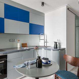 На фото: угловая кухня среднего размера в современном стиле с обеденным столом, накладной раковиной, плоскими фасадами, синими фасадами, белым фартуком, фартуком из стекла, черной техникой, полом из керамогранита и серой столешницей без острова с