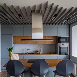 Свежая идея для дизайна: большая параллельная кухня-гостиная в современном стиле с накладной раковиной, плоскими фасадами, серыми фасадами, деревянной столешницей, серым фартуком, фартуком из стекла, техникой из нержавеющей стали, паркетным полом среднего тона, островом, коричневым полом и коричневой столешницей - отличное фото интерьера