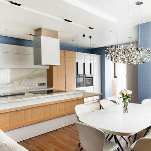 Пример оригинального дизайна интерьера: кухня-гостиная среднего размера в современном стиле с плоскими фасадами, белыми фасадами, белым фартуком, островом, белой столешницей, мраморной столешницей, фартуком из мрамора и паркетным полом среднего тона