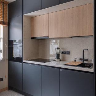 На фото: кухня в современном стиле с накладной раковиной, плоскими фасадами, серыми фасадами, техникой из нержавеющей стали, белым полом и серой столешницей с