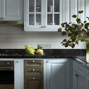 На фото: кухня в классическом стиле с накладной раковиной, фасадами с выступающей филенкой, черной столешницей, столешницей из гранита, темным паркетным полом и коричневым полом с