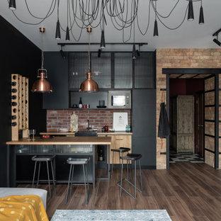 Идея дизайна: п-образная кухня-гостиная среднего размера в стиле лофт с черными фасадами, деревянной столешницей, черной техникой, коричневым полом, раковиной в стиле кантри, плоскими фасадами, красным фартуком, фартуком из кирпича, паркетным полом среднего тона, полуостровом и бежевой столешницей