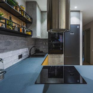 На фото: маленькая п-образная кухня в современном стиле с накладной раковиной, плоскими фасадами, серыми фасадами, черной техникой, полуостровом, серым фартуком, фартуком из плитки кабанчик, бежевым полом и синей столешницей с