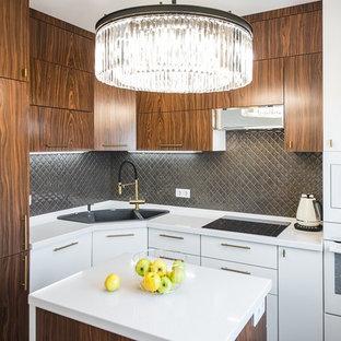 На фото: маленькая отдельная, угловая кухня в современном стиле с накладной раковиной, плоскими фасадами, фасадами цвета дерева среднего тона, серым фартуком, белой техникой, островом и белой столешницей с