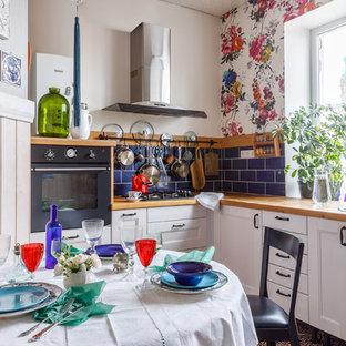 Стильный дизайн: отдельная, угловая кухня в стиле кантри с фасадами с утопленной филенкой, белыми фасадами, синим фартуком, черной техникой и коричневой столешницей - последний тренд