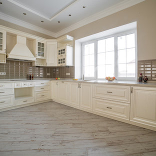 Inspiration for a large country u-shaped eat-in kitchen in Moscow with an undermount sink, raised-panel cabinets, beige cabinets, solid surface benchtops, brown splashback, ceramic splashback, white appliances, ceramic floors, no island, beige floor and beige benchtop.