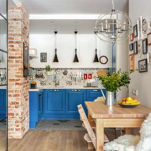 Пример оригинального дизайна: маленькая п-образная кухня в скандинавском стиле с врезной раковиной, фасадами с выступающей филенкой, синими фасадами, разноцветным фартуком и белой столешницей без острова