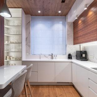 Стильный дизайн: отдельная, угловая кухня в современном стиле с монолитной раковиной, плоскими фасадами, белыми фасадами, белым фартуком, техникой под мебельный фасад, паркетным полом среднего тона, коричневым полом и белой столешницей - последний тренд