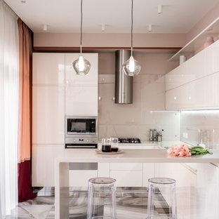 На фото: п-образная кухня в современном стиле с плоскими фасадами, белыми фасадами, серым фартуком, техникой из нержавеющей стали, полуостровом, серым полом и серой столешницей