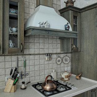Неиссякаемый источник вдохновения для домашнего уюта: кухня в стиле кантри с фасадами с выступающей филенкой, фасадами цвета дерева среднего тона, серым фартуком и серой столешницей