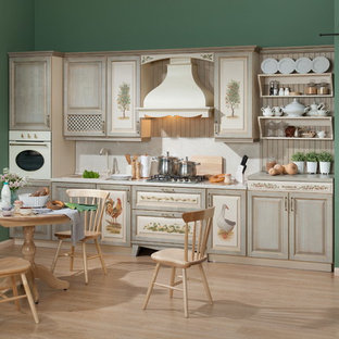 Design ideas for a large country single-wall separate kitchen in Moscow with a single-bowl sink, raised-panel cabinets, beige cabinets, laminate benchtops, beige splashback, coloured appliances, laminate floors, no island, brown floor and beige benchtop.