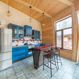 На фото: параллельная кухня в современном стиле с обеденным столом, накладной раковиной, фасадами в стиле шейкер, синими фасадами, красным фартуком, фартуком из плитки кабанчик, техникой из нержавеющей стали, островом, серым полом и красной столешницей