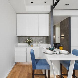 Неиссякаемый источник вдохновения для домашнего уюта: угловая кухня-гостиная в современном стиле с монолитной раковиной, плоскими фасадами, белыми фасадами, серым фартуком, белой техникой, паркетным полом среднего тона и коричневым полом