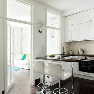 Неиссякаемый источник вдохновения для домашнего уюта: п-образная кухня в современном стиле с накладной раковиной, плоскими фасадами, белыми фасадами, бежевым фартуком, техникой из нержавеющей стали и коричневым полом без острова