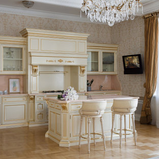 Photo of a victorian galley eat-in kitchen in Saint Petersburg with raised-panel cabinets, white cabinets, pink splashback, stone slab splashback, light hardwood floors, with island, beige floor and pink benchtop.