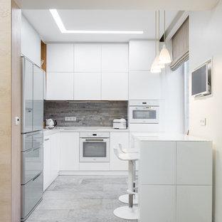 Новый формат декора квартиры: угловая кухня-гостиная среднего размера в скандинавском стиле с плоскими фасадами, белыми фасадами, столешницей из кварцевого композита, серым фартуком, фартуком из керамогранитной плитки, белой техникой и полом из керамогранита без острова