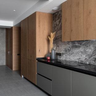 Ejemplo de cocina lineal, contemporánea, con armarios con paneles lisos, puertas de armario de madera oscura, encimera de acrílico, salpicadero verde, salpicadero de mármol, electrodomésticos negros, suelo de baldosas de porcelana, suelo gris y encimeras negras