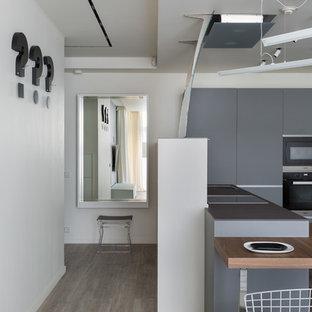 Свежая идея для дизайна: кухня в скандинавском стиле с плоскими фасадами, серыми фасадами, черной техникой и паркетным полом среднего тона - отличное фото интерьера