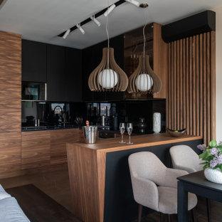 На фото: угловая кухня среднего размера в современном стиле с обеденным столом, плоскими фасадами, фасадами цвета дерева среднего тона, черным фартуком, фартуком из стекла, черной техникой, темным паркетным полом, полуостровом, коричневым полом и черной столешницей с